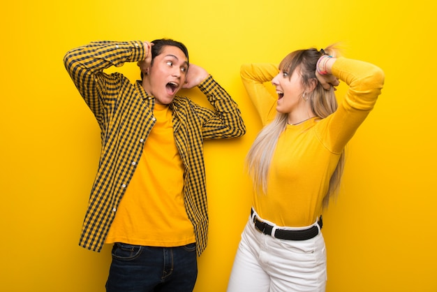 Young couple over vibrant yellow background with surprise and shocked