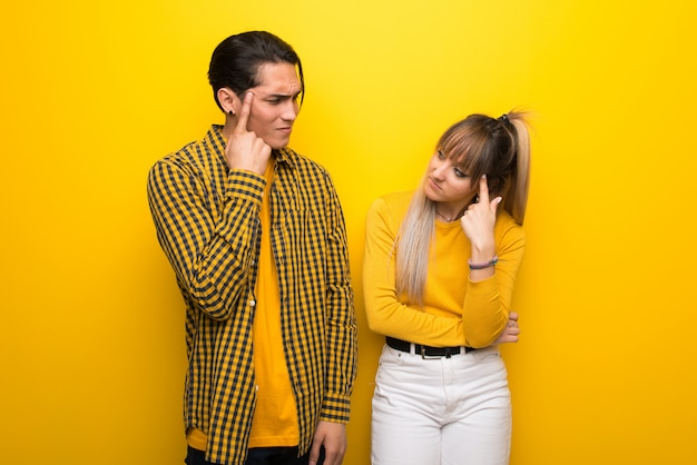 Young couple over vibrant yellow background