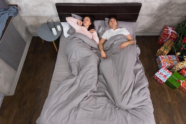 若いカップルはプレゼントとクリスマスツリーの近くの家でパジャマを着て目を覚ます