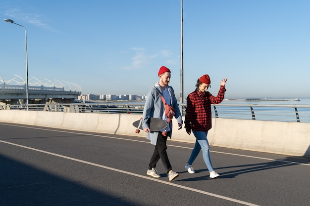 Young couple walk on bridge together talk stylish hipsters date over urban skyline youth lifestyle