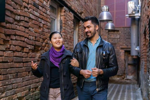 Young couple walking along an old alley and talking