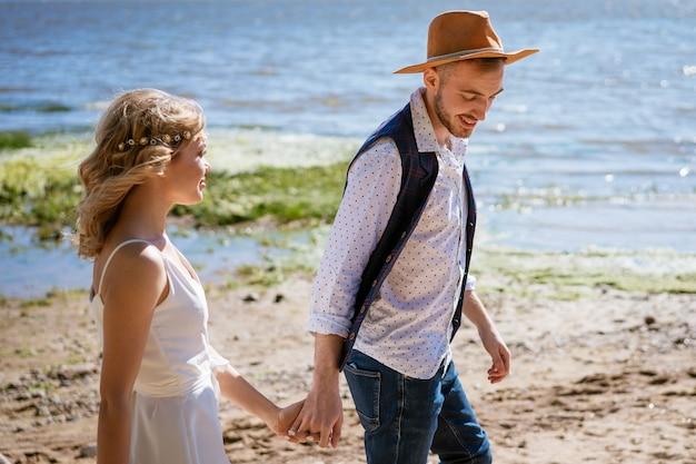 Молодая пара гуляет по пляжу в солнечный летний день