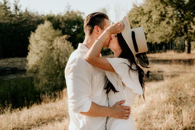 Молодая пара прогулки и поцелуи на летнем лугу на закате