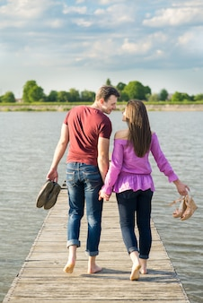 Young couple walking barefoot by wooden bridge on the lake