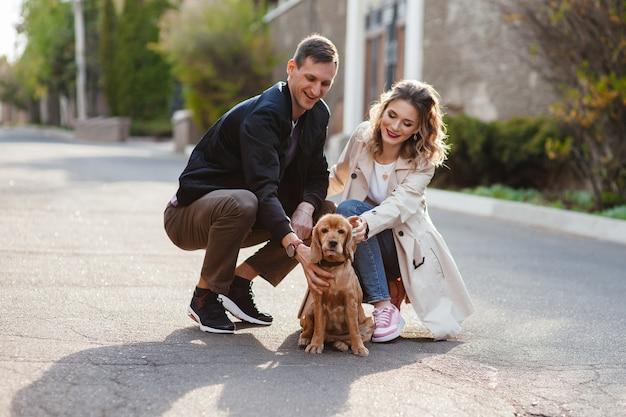 街の通りで犬と一緒に階段を歩いている若いカップル
