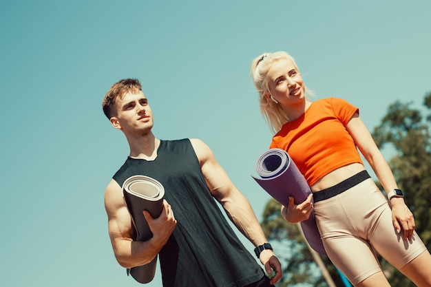 Young couple walking down the street with sports mats in their hands