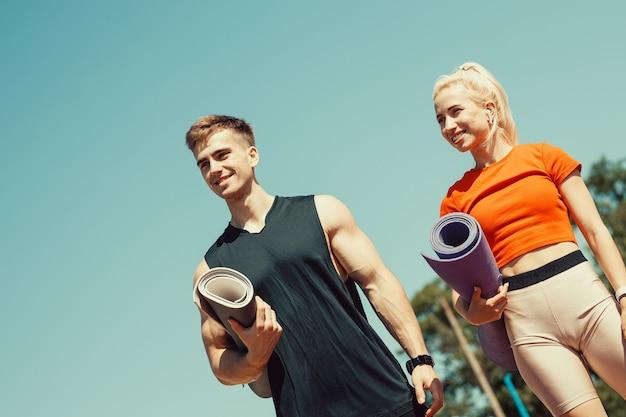 Молодая пара идет по улице со спортивными ковриками в руках