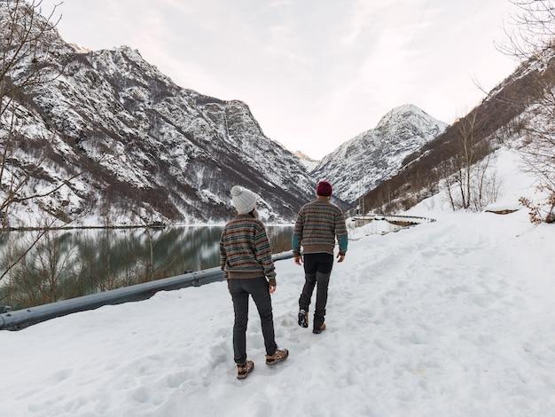 湖のほとりの雪の中を歩く冬服を着て歩く若いカップル。