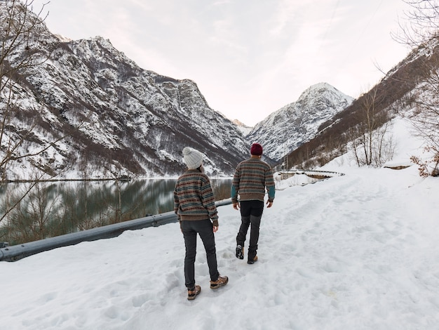 Young couple walking dressed alike in winter clothes walking in the snow beside a lake.