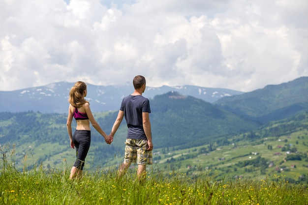 Young couple walking holding hands outdoors.
