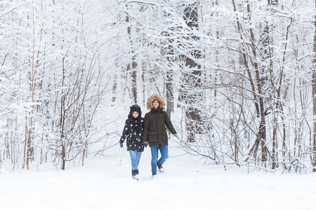 눈 덮인 공원에서 산책 하는 젊은 부부. 겨울 시즌.