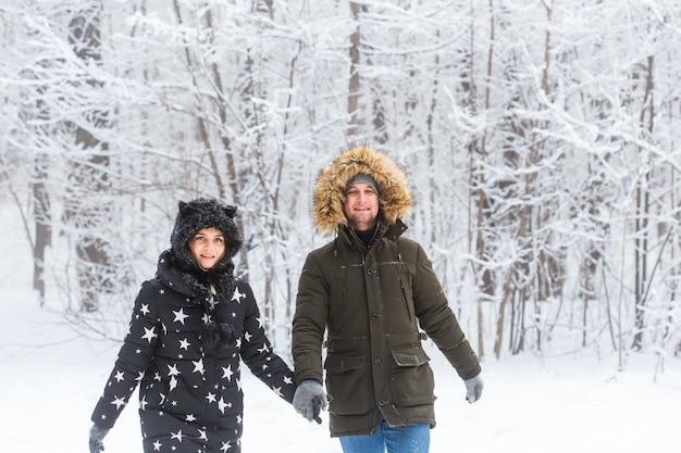 Молодая пара, прогулки в снежном парке. зимний сезон.