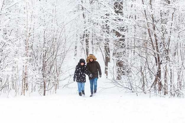 Молодая пара гуляет в снежном парке зимой