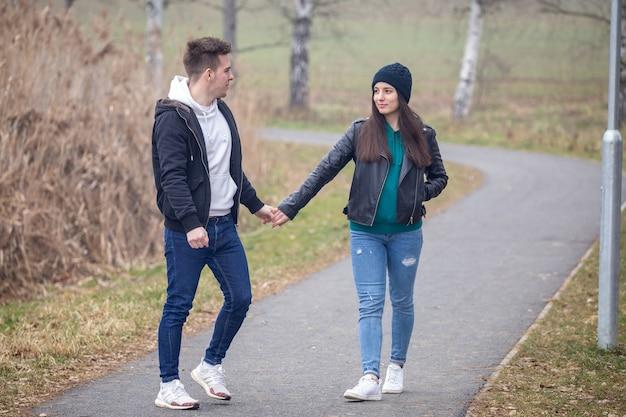 霧の冬の日に自然の中を歩き、お互いを見つめる若いカップル