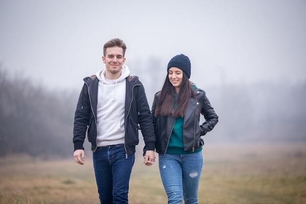 Молодая пара гуляет на природе в туманный зимний день