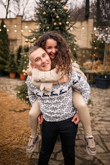 Молодая пара гуляет в рождественском саду возле елки
