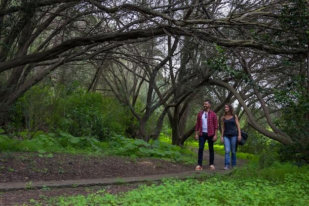 그란 카나리아의 식물원에서 큰 나뭇 가지 아래 숲길을 걷는 젊은 부부