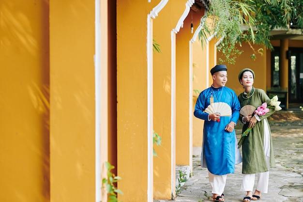 조각된 부채와 연꽃이 있는 베트남 전통 의상을 입고 야외에서 걷는 젊은 부부