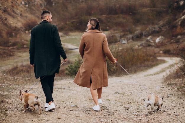Молодая пара прогулки своих французских бульдогов в парке