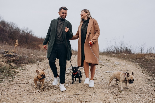 Giovani coppie che camminano i loro bulldog francesi in parco