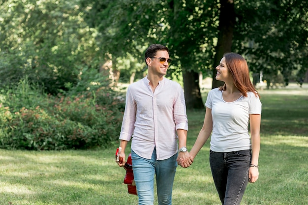 Young couple walking through green field