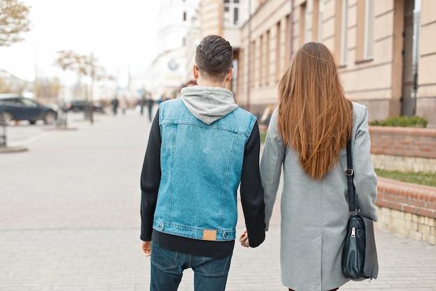 後ろから街の景色を歩く若いカップル