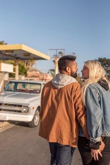 Молодая пара идет к машине, держась за руки