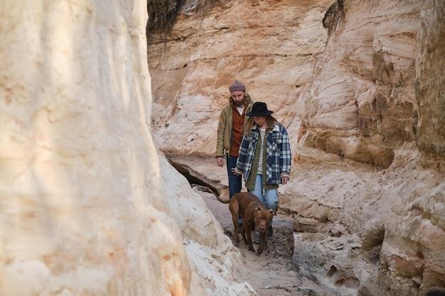 屋外の岩に沿って犬と一緒に歩いている若いカップル
