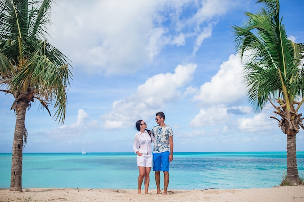 Young couple walking on tropical beach with white sand and turquoise ocean water in caribbean