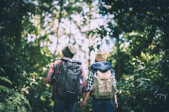 Young couple walking with backpacks in forest