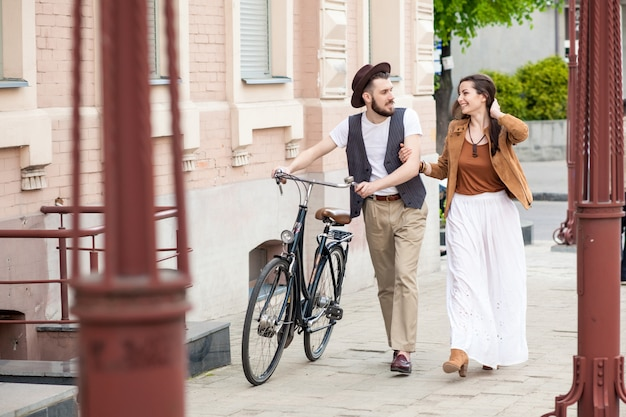 Молодая пара гуляет с велосипедом и обнимает