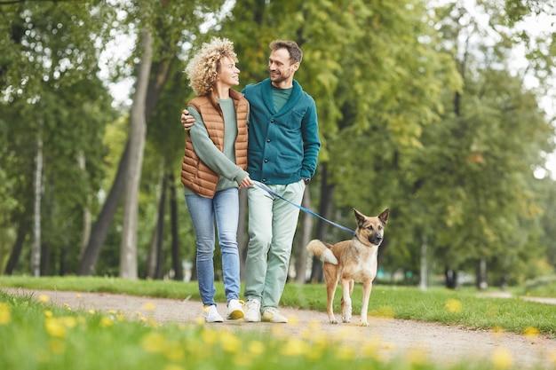 Молодая пара гуляет с собакой вместе в парке на открытом воздухе