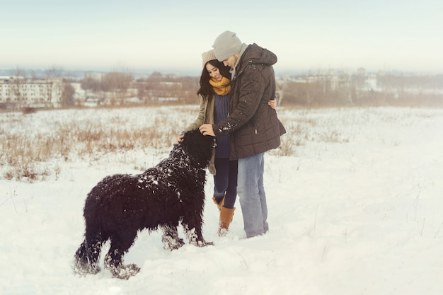 Young couple walking with a dog in a winter day