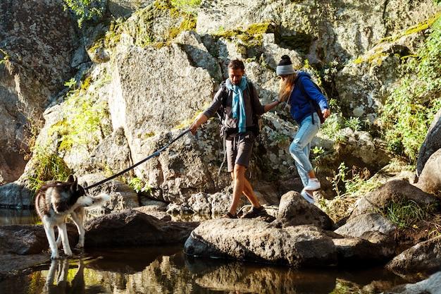 水の近くの峡谷でハスキー犬と歩く若いカップル