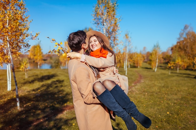 Young couple walks in autumn forest. man carrying his girlfriend in hands and laughing