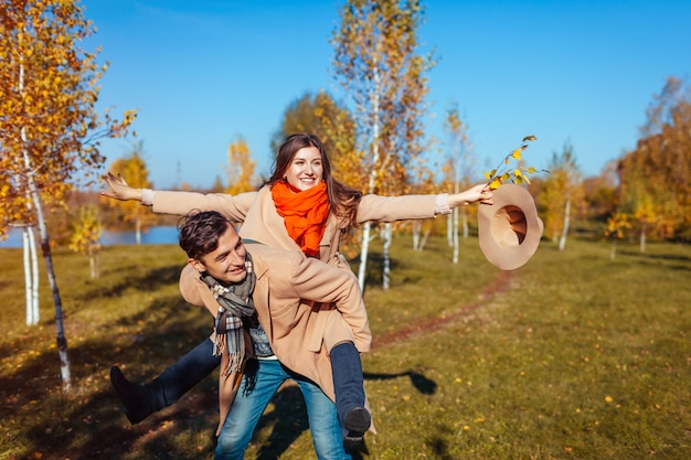 Young couple walks in autumn forest. man giving his girlfriend piggyback. people having fun