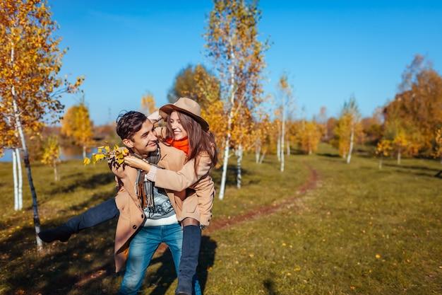 若いカップルは秋の森を歩きます。彼のガールフレンドを便乗させる男。屋外で楽しんでいる人