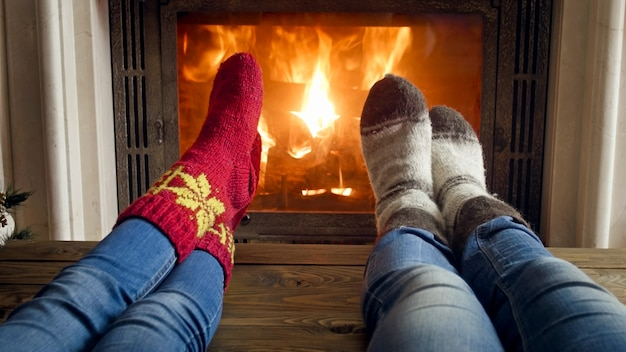 Young couple in warm knitted socks relaxing in chalet at fireplace