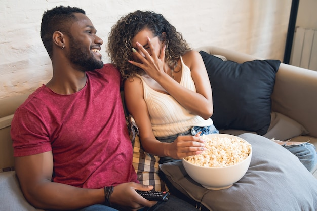 Giovani coppie che guardano un film dell'orrore seduti su un divano a casa.