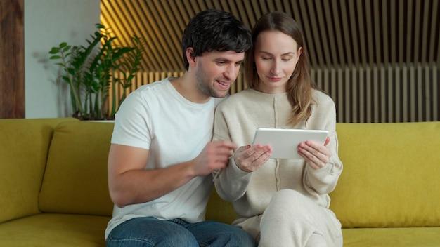 집에서 소파에 앉아 태블릿에서 온라인 미디어 콘텐츠를 시청하는 젊은 부부