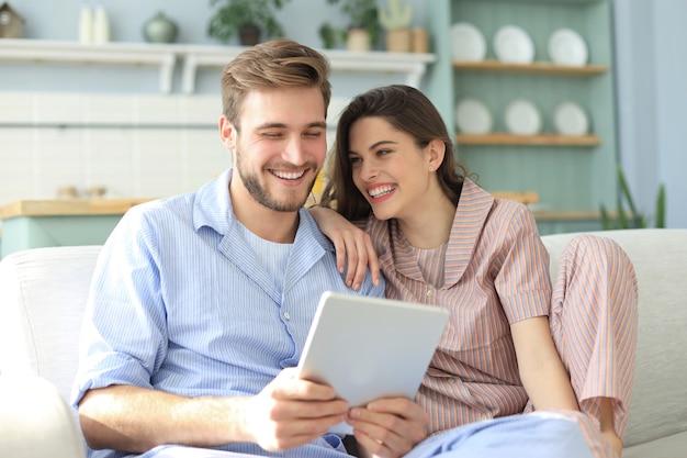 Молодая пара смотрит медиа-контент онлайн в планшете, сидя на диване в гостиной.