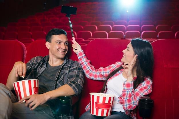 映画館で映画を見ている若いカップル
