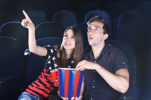 Молодая пара смотрит фильм в кино