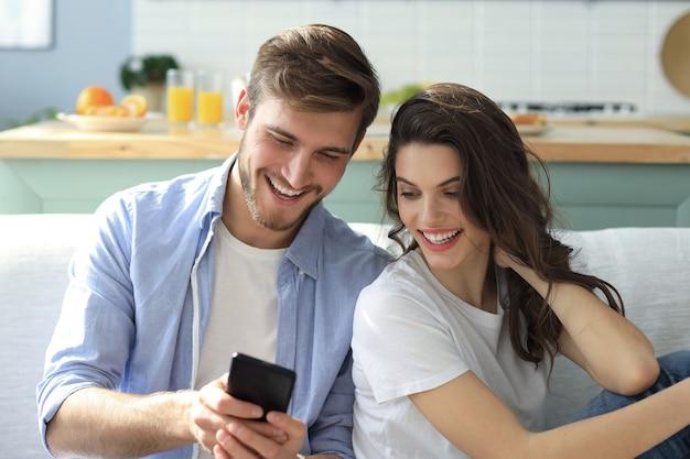 リビングルームの自宅のソファに座ってスマートフォンでオンラインコンテンツを見ている若いカップル。