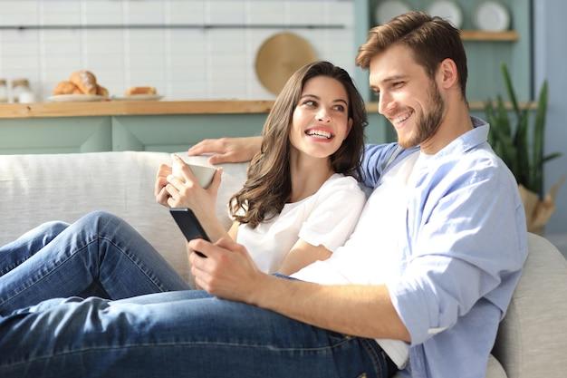 Молодая пара смотрит онлайн-контент в смартфоне, сидя на диване у себя дома в гостиной.