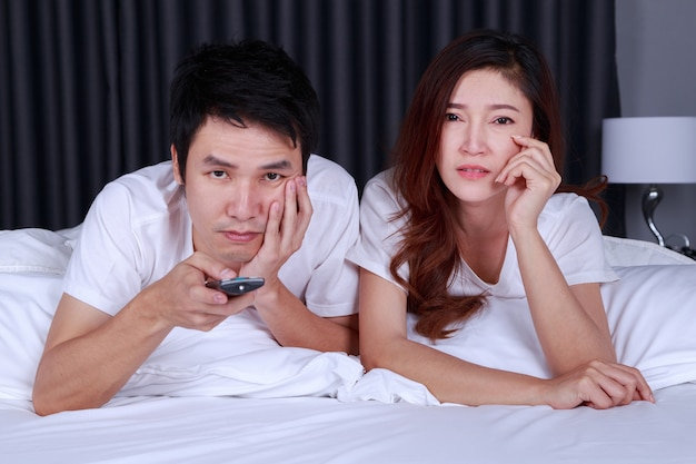Young couple watching sad movie on bed in bedroom