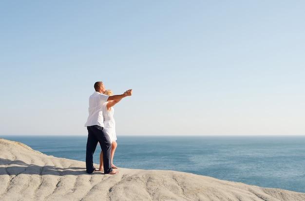 Молодая пара смотрит на море, взявшись за руки