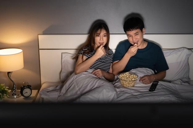 밤에 침대에서 tv를 보고 팝콘을 먹는 젊은 부부