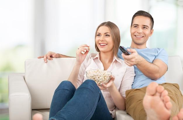家でテレビを見ている若いカップル
