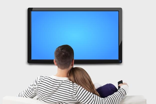 Молодая пара смотрит телевизор дома